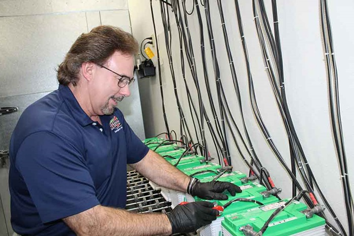 Jeff Barron, wearing safety glasses and gloves, inspects recently frozen batteries.