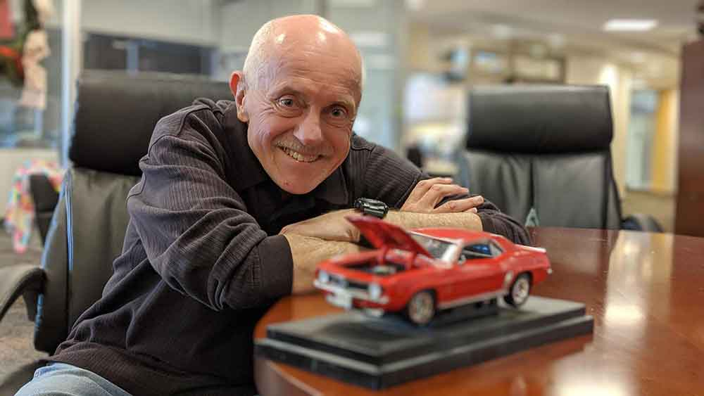 Interstate Expert Joe Semens holds a model car with the hood up.