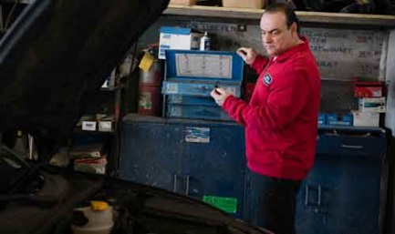 Ralph Parente of Soundview Service Center looks at a aftermarket auto part for a car